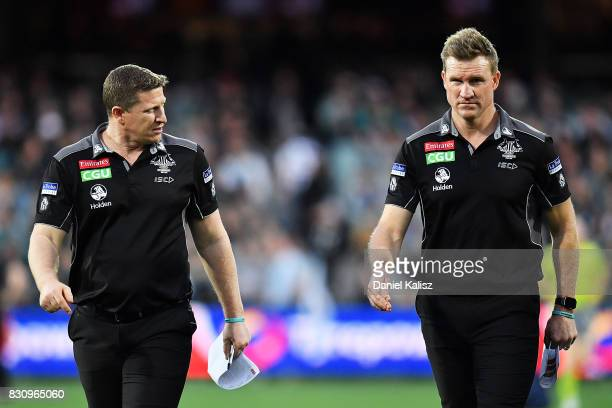Magpies midfield coach Scott Burns and Magpies head coach Nathan Buckley walk from the field during the round 21 AFL match between Port Adelaide...