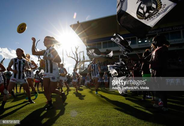 Magpies players run onto the field during the 2018 AFLW Round 04 match between the Melbourne Demons and the Collingwood Magpies at TIO Traeger Park...