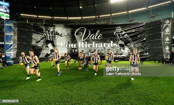 Magpies players run through a banner honoring Lou Richards during the 2017 AFL round 09 match between the Collingwood Magpies and the Hawthorn Hawks...