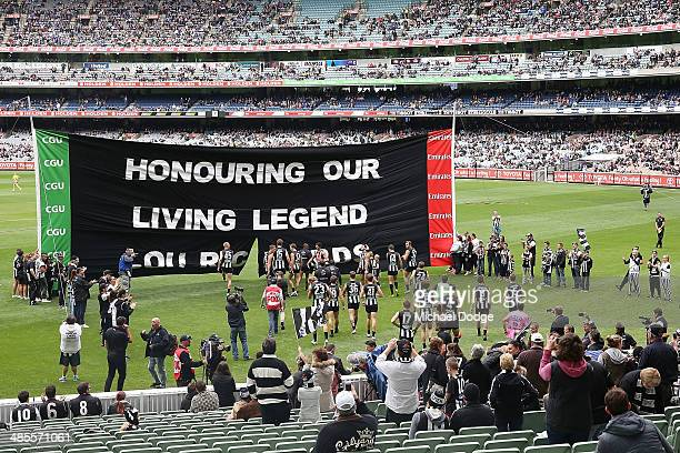 Magpies players walk to the banner dedicated to Lou Richards during the round five AFL match between the Collingwood Magpies and the North Melbourne...