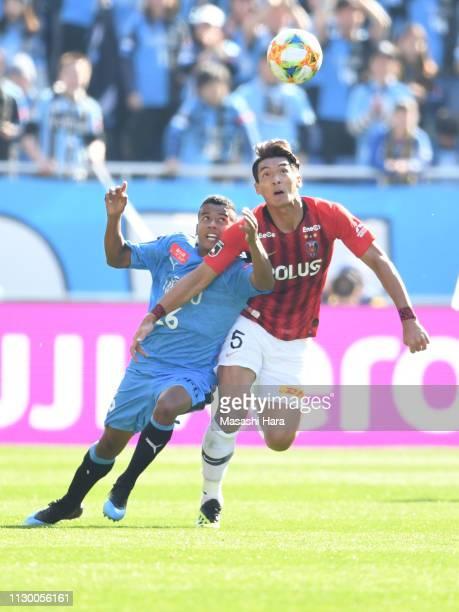 Maguinho of Kawasaki Frontale and Tomoaki Makino of Urawa Red Diamonds compete for the ball during the Fuji Xerox Super Cup between Kawasaki Frontale...