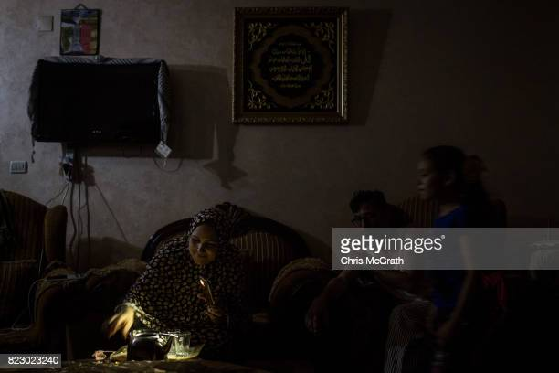 Maha Zant prepares tea for her husband Rami by cell phone light at her home in the AlZahra district on July 23 2017 in Gaza City Gaza For the past...