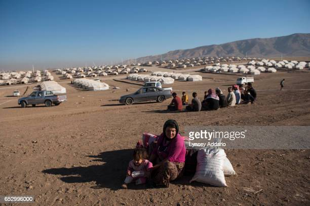 Mahabat an Iraqi Yazidi woman from Siba Sheikh Khadir village in Sinjar sits with two of her five children while waiting to receive a tent from the...