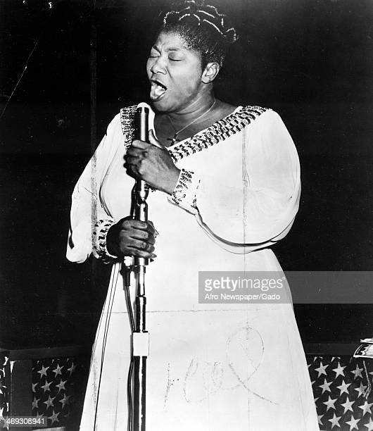 Mahalia Jackson Gospel singer singing into microphone with her eyes closed 1959