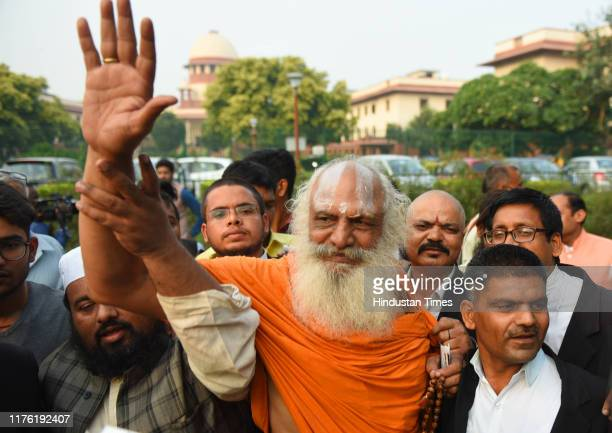 Mahant Dharam Das Ayodhya case litigant and leader of the Ram Janmabhoomi movement poses for a picture with lawyers and other supporters after the...