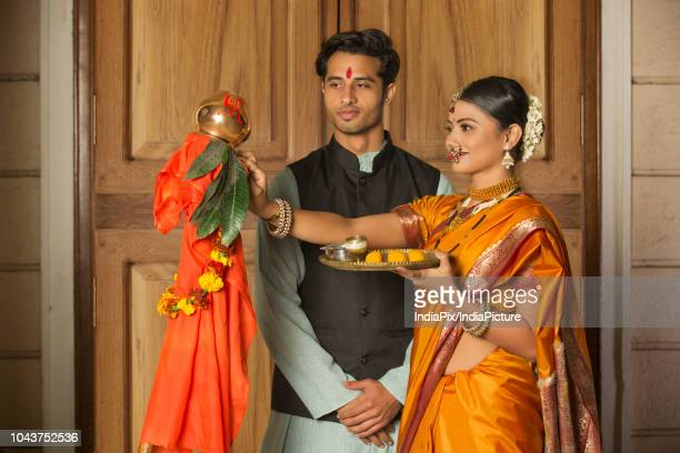 maharashtrian couple in traditional dress celebrating gudi padwa festival holding a pooja plate. - gudi padwa stock pictures, royalty-free photos & images