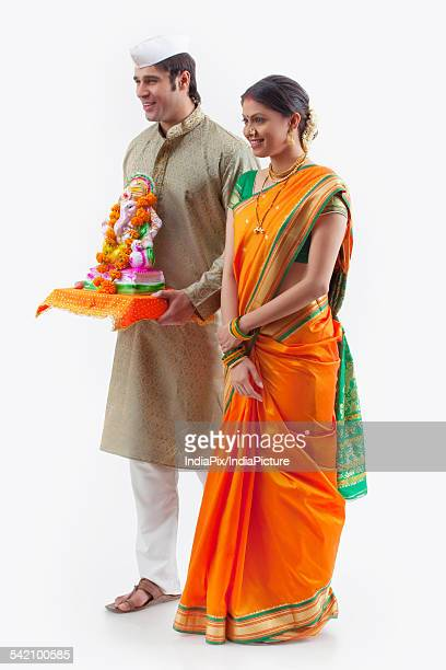 maharashtrian couple with a ganesh idol - ganesh chaturthi stock photos and pictures