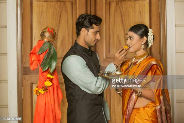 maharashtrian man in traditional dress offering sweet to her wife while celebrating gudi padwa festival. - gudi padwa stock pictures, royalty-free photos & images