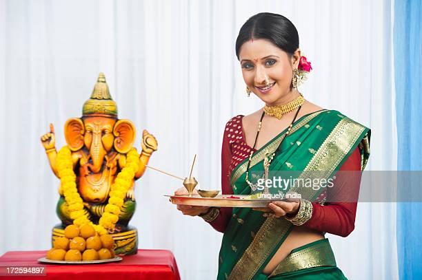 Maharashtrian woman holding a puja thali during Ganesh Chaturthi festival