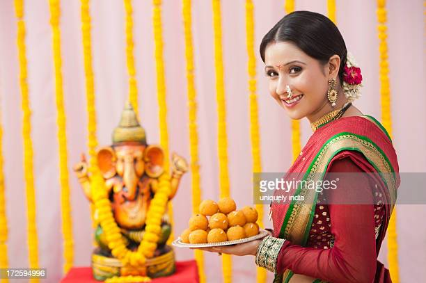 Maharashtrian woman holding laddu in a plate during ganesh chaturthi festival