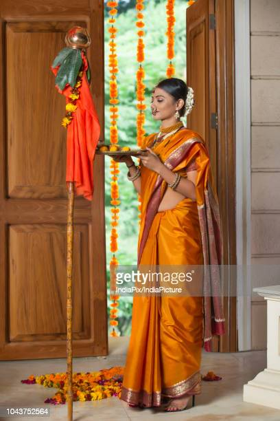 Maharashtrian woman in traditional dress praying with eyes closed while celebrating gudi padwa festival holding a pooja plate.