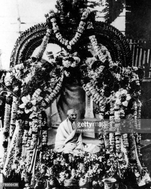 Mahatma Gandhi India's spiritual leader rides on a car through the streets of Madras India bedecked with garlands