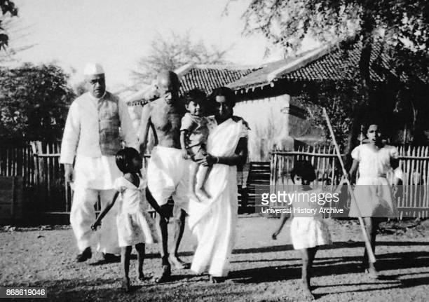 Mahatma Gandhi walking with his grand daughter in law Saraswati her son Shanti and others at Sevagram Ashram 1940