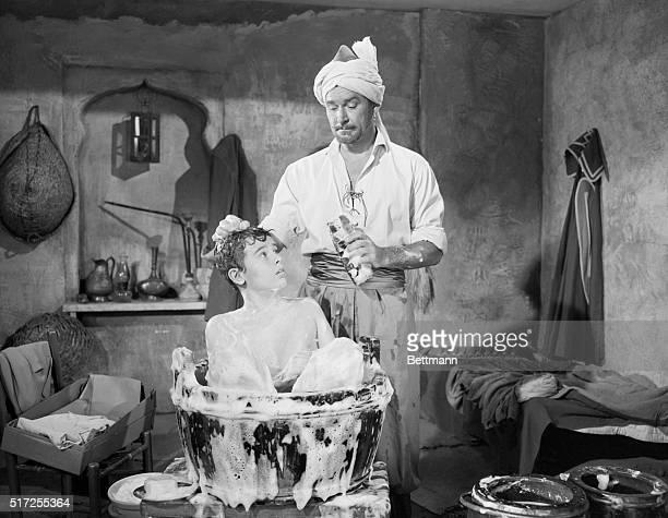 Mahbub Ali gives Kim a bubble bath in a scene from the 1950 adventure film Kim