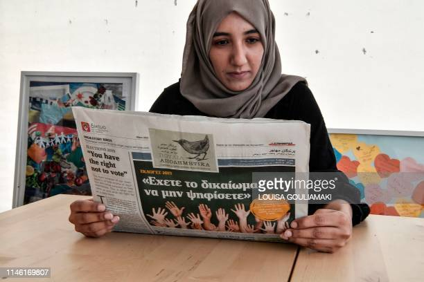 Mahdia Hosseini Afghan editorinchief of the Migratory Birds newspaper reads the newspaper's special edition related to the European elections issued...
