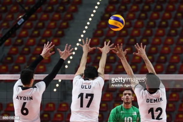 Mahdjoubi Toufik of Algeria spikes the ball against Aydin Yasin Ulu Dogukan and Demir Selim of Turkey during the Men's Volleyball Bronze medal match...