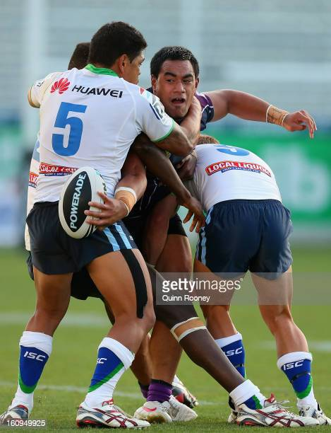 Mahe Fonua of the Storm attempts to pass the ball whilst being tackled during the NRL trial match between the Melbourne Storm and the Canberra...