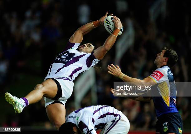 Mahe Fonua of the Storm catches a high ball over Ashley Graham of the Cowboys during the round two NRL match between the North Queensland Cowboys and...