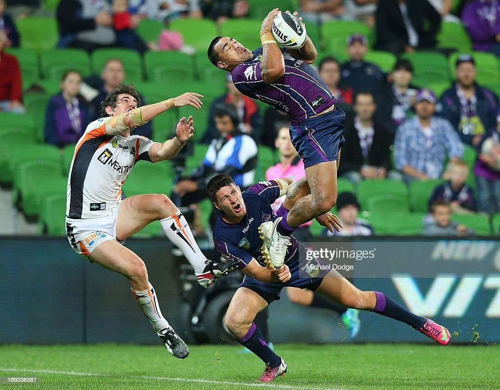 Mahe Fonua of the Storm catches the ball over Joel Reddy of the Tigers and teamate Gareth Widdop during the round 5 NRL match between the Melbourne Storm and the Wests Tigers at AAMI Stadium on April 8, 2013 in Melbourne, Australia.