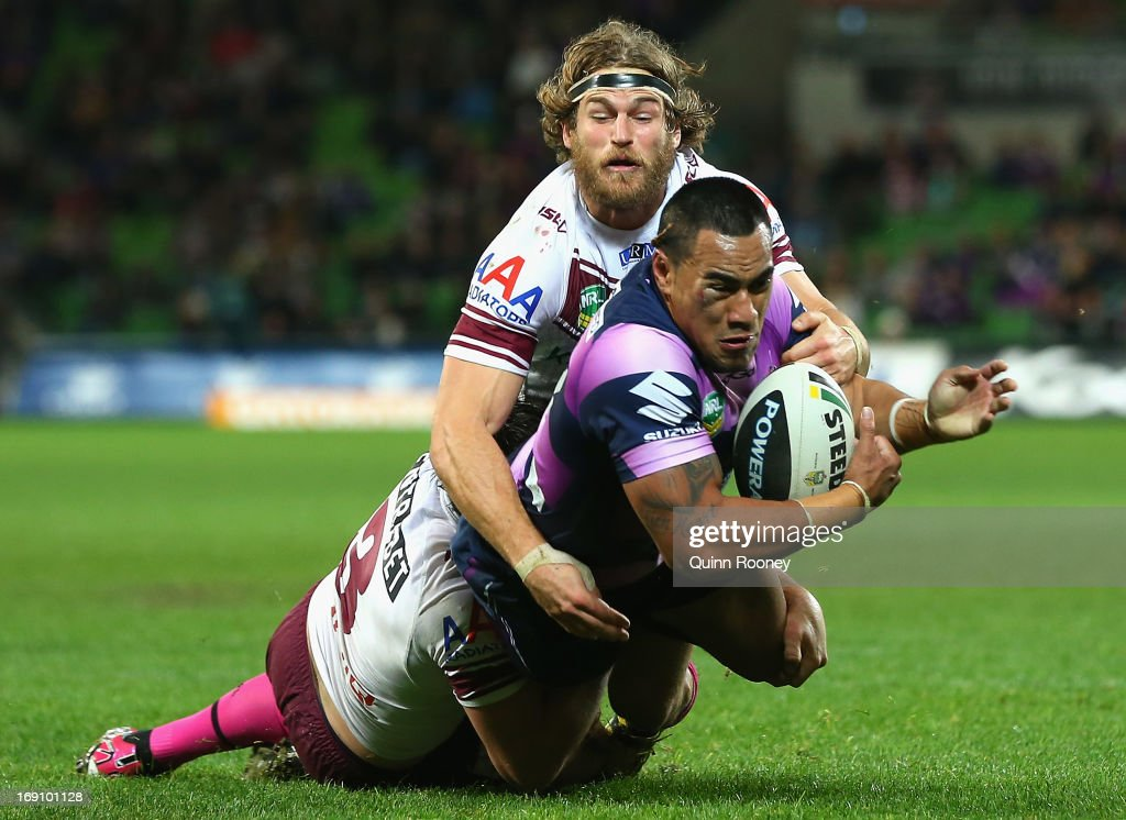Mahe Fonua of the Storm is tackled by Jamie Lyon and David Williams of the Sea Eagles during the round 10 NRL match between the Melbourne Storm and the Manly Sea Eagles at AAMI Park on May 20, 2013 in Melbourne, Australia.