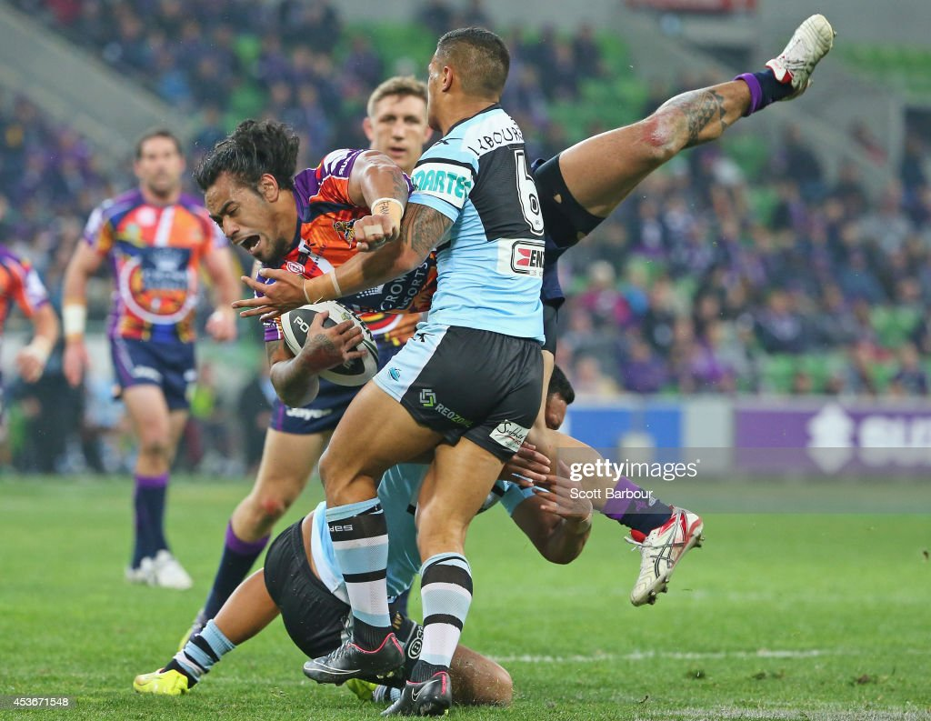 Mahe Fonua of the Storm is tackled during the round 23 NRL match between the Melbourne Storm and the Cronulla Sharks at AAMI Park on August 16, 2014 in Melbourne, Australia.
