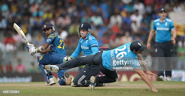 Mahela Jayawardena of Sri Lanka hits past Jos Buttler and England captain Alastair Cook during the 2nd One Day International match between Sri Lanka...