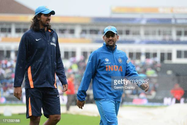 Mahendra Singh Dhoni and Ishant Sharma of India walk back to the dressing room after rain begins to fall prior to the ICC Champions Trophy Final...