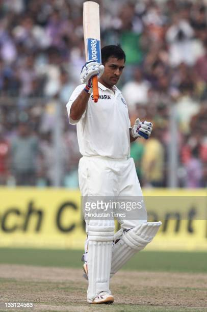Mahendra Singh Dhoni of India raises his bat after scoring a century during the second day of second Test Match between India and West Indies at Eden...