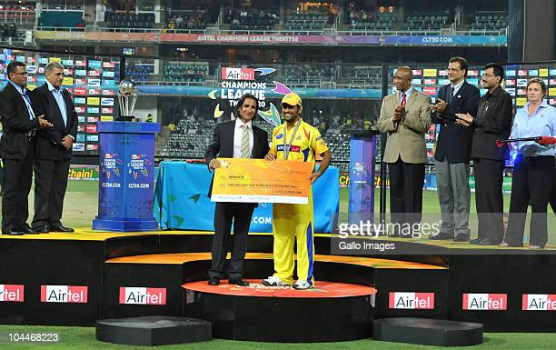Mahendra Singh Dhoni of the Kings receives his winnings during the 2010 Airtel Champions League Twenty20 final match between Chennai Super Kings and...