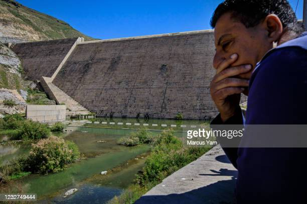 Maher Tahtamouni looks on at the Yarmouk river, a waterway that flows through the al-Wehda Dam, a 360-foot concrete embankment, near Harta, Jordan,...