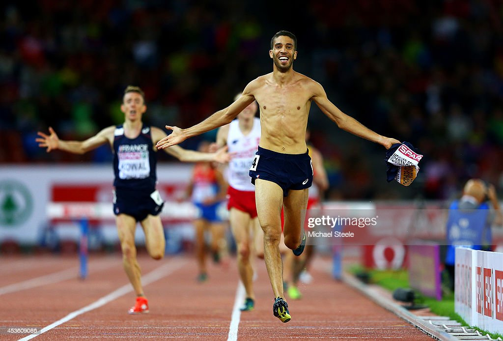 Mahiedine Mekhissi-Benabbad of France takes his vest off as he approaches the finish line to claim gold ahead of Yoann Kowal of France in the Men's 3000 metres Steeplechase final during day three of the 22nd European Athletics Championships at Stadium Letzigrund on August 14, 2014 in Zurich, Switzerland.