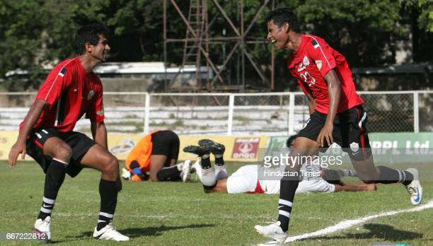 Mahindra United's Sreven Dias and Mohd Rafi celebrate after steven scord a goal as Pune FC goal keeper Subrata Paul and his teammate Sunil Kumar lie...