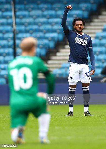 Mahlon Romeo of Millwall FC raising his right fist as Barry Bannan of Sheffield Wednesday takes the knee in support of the Black Lives Matter...