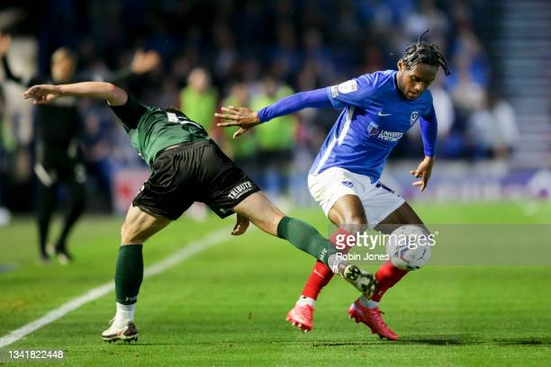 Mahlon Romeo of Portsmouth FC beats Conor Grant to the ball during the Sky Bet League One match between Portsmouth and Plymouth Argyle at Fratton...