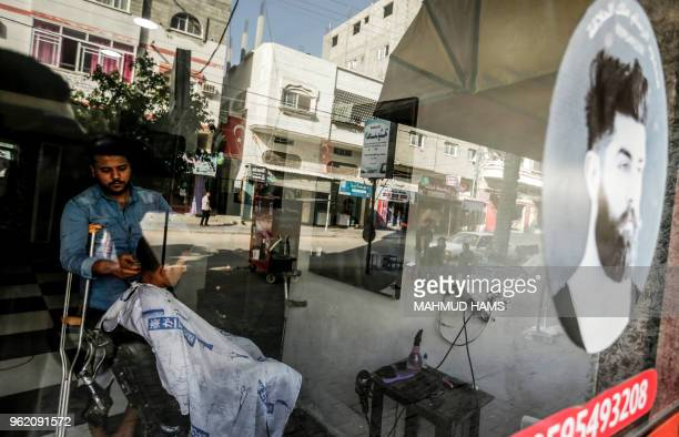 TOPSHOT Mahmoud Abu Shaweesh a 28yearold Palestinian barber who was wounded in the leg during clashes with Israeli security forces at the GazaIsraeli...