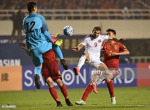 Mahmoud Almawas of Syria kicks the ball against Chinese goalkeeper Chao Gu during the 2018 World Cup qualifying group A match between Syria and China...