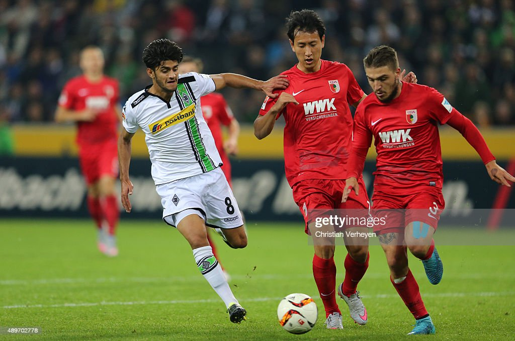 Mahmoud Dahoud of Borussia Moenchengladbach, Jeong-Ho Hong and Konstantinos Stafylidis of FC Augsburg battle for the ball during the Bundesliga match between Borussia Moenchengladbach and FC Augsburg at Borussia-Park on September 23, 2015 in Moenchengladbach, Germany