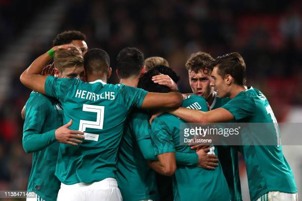Mahmoud Dahoud of Germany celebrates with team mates after scoring his sides first goal during the International Friendly match between England u21's...