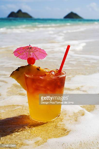 A mai tai garnished with pinapple and a cherry, sitting in shallow water on the beach.