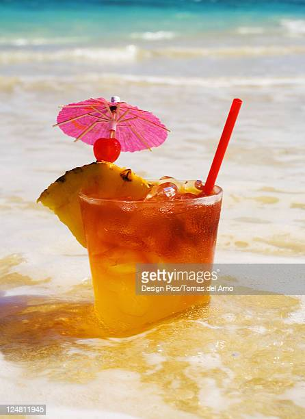 a mai tai garnished with pinapple and a cherry, sitting in shallow water on the beach. - mai tai fotografías e imágenes de stock
