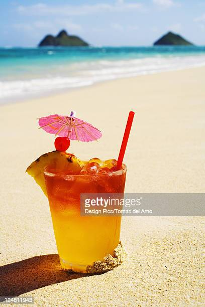 a mai tai garnished with pinapple and a cherry, sitting in the sand on the beach. - mai tai fotografías e imágenes de stock