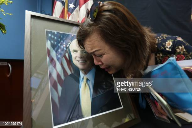 TOPSHOT Mai Tran an American of Vietnamese descent grieves over the portrait of the late US Senator John McCain during a memorial tribute at the US...