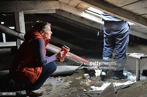 Maia Morgenstern the director of the Romanian State Jewish Theatre kneels on the attic of the teatre as she inspects the damaged roof in Bucharest...