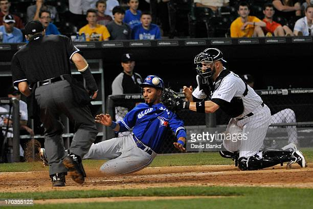Maicer Izturis of the Toronto Blue Jays is safe at home as Tyler Flowers of the Chicago White Sox drops the ball during the tenth inning on June 11...