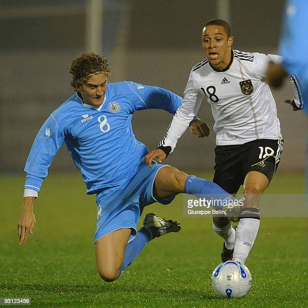 Maicol Berretti of San Marino and Sidney Sam of Germany battle for the ball during the UEFA U21 Championship match between San Marino and Germany at...