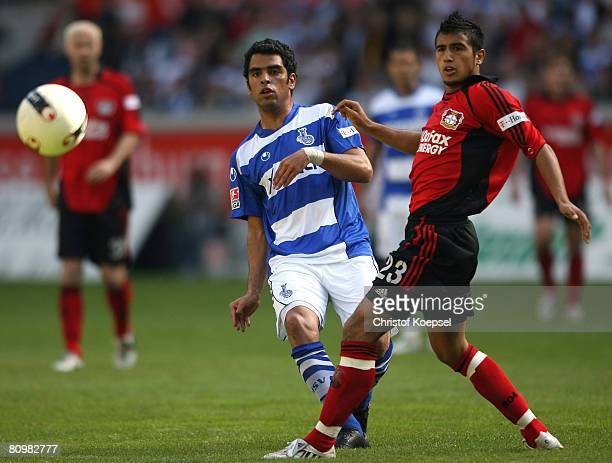 Maicon of Duisburg takes a shot at the goal and Arturo Vidal of Leverkusen tries to block him during the Bundesliga match between MSV Duisburg and...