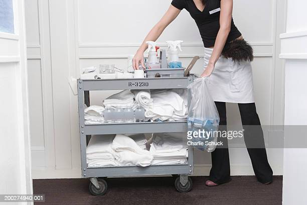 Maid by trolley in hotel corridor, low section