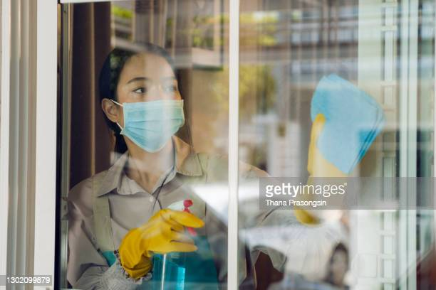 maid cleaning windows of a house - formal glove stock pictures, royalty-free photos & images