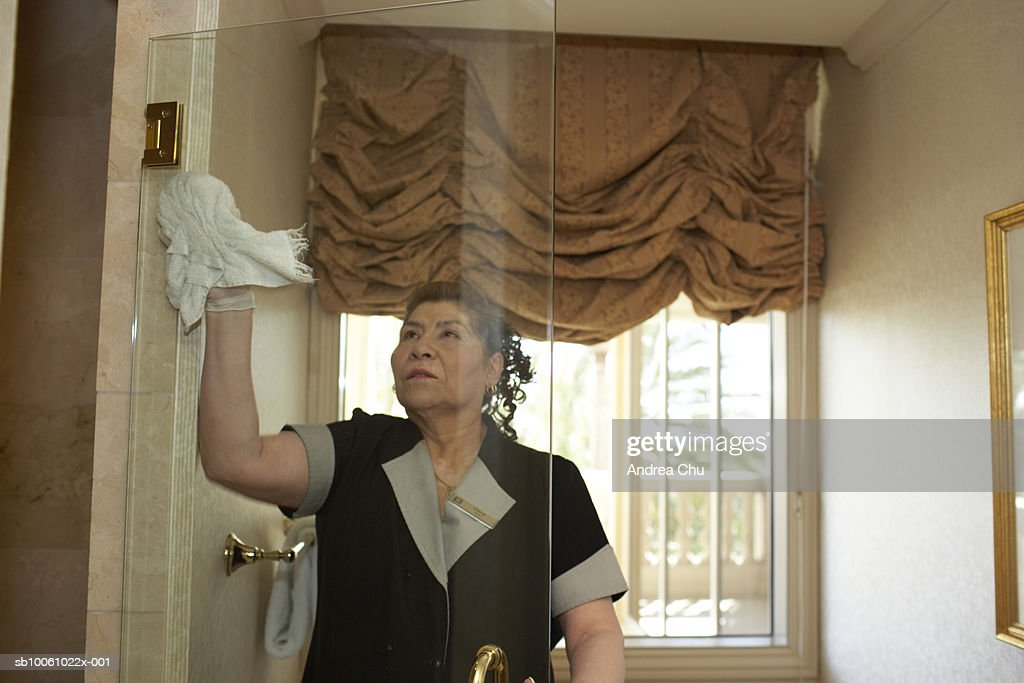 Maid Clearing Glass Door In Hotel Bathroom Stock Photo Getty Images - Bathroom maid