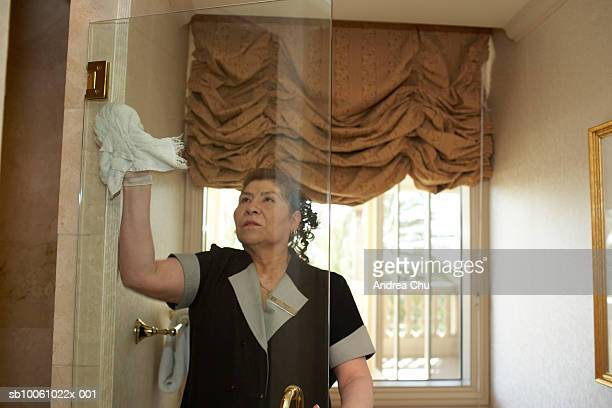 maid clearing glass door in hotel bathroom - maid stock pictures, royalty-free photos & images